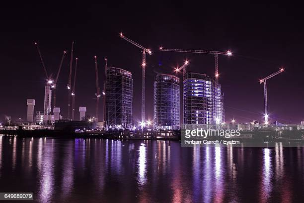 illuminated incomplete buildings by thames river against sky - waterfront stock pictures, royalty-free photos & images