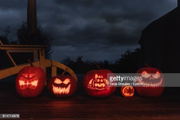 illuminated jack o lanterns on table at night - halloween lantern stock photos and pictures