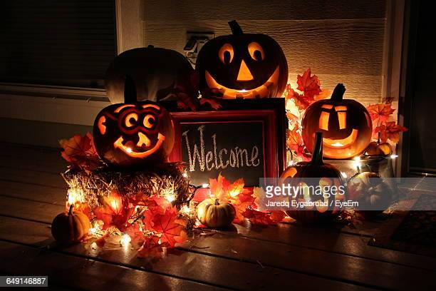 illuminated jack o lanterns with welcome sign - halloween lantern stock photos and pictures