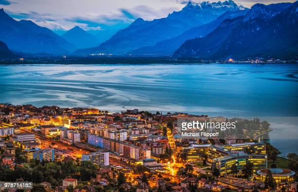 illuminated lakeside city during dusk, vevey, switzerland - kanton waadt stock-fotos und bilder