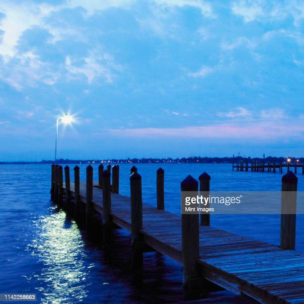 illuminated lamp at edge of dock on lake at dusk - palmetto florida stock pictures, royalty-free photos & images