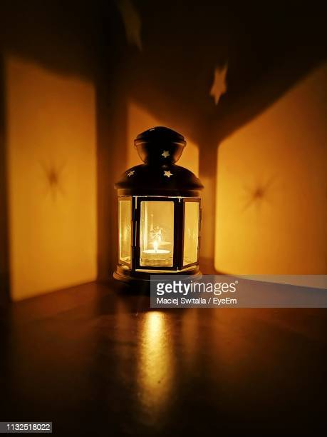 illuminated lamp on table against wall at home - oil lamp stock pictures, royalty-free photos & images