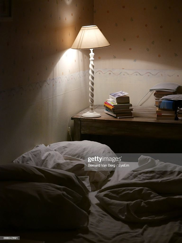 Illuminated Lamp On Table By Bed In Room : Stock Photo