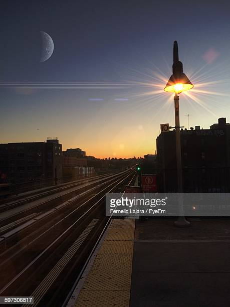 illuminated lamp post at railroad station against sky during sunset - the bronx stock pictures, royalty-free photos & images
