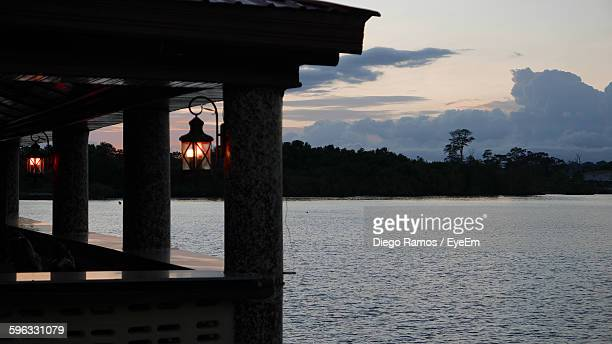 illuminated lamp shade in house by river against cloudy sky - malabo stock pictures, royalty-free photos & images