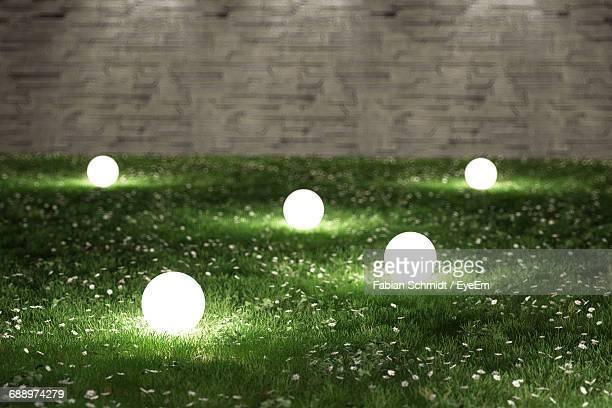 illuminated lamps on grassy field in garden - lamp stock-fotos und bilder