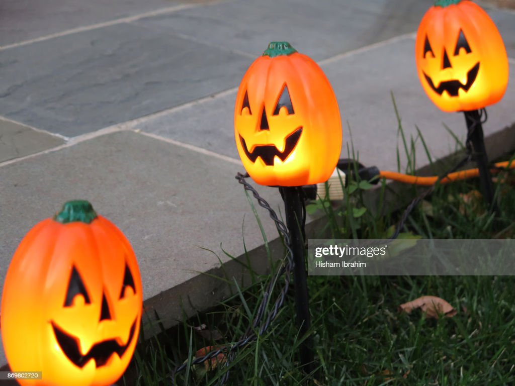 Illuminated landscape light fixtures in the shape of pumpkins used for Halloween decoration at night. : Stock Photo