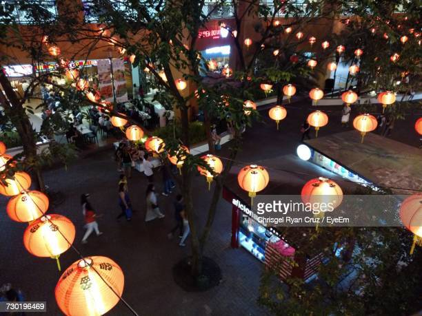 illuminated lanterns hanging on street at night - manila stock pictures, royalty-free photos & images