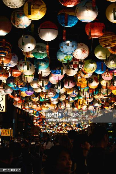 illuminated lanterns hanging over people in market at night - chinese lantern festival stock pictures, royalty-free photos & images