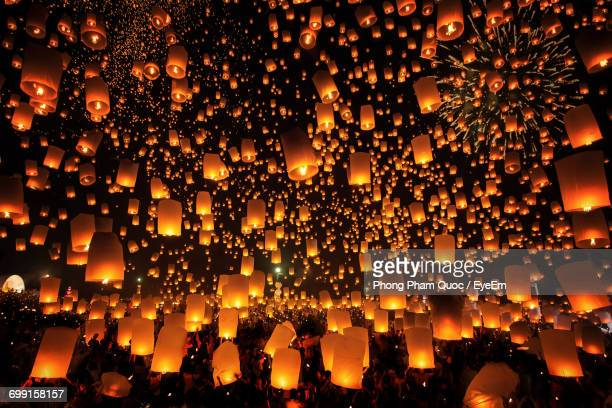 illuminated lanterns over crowd in city at night during yi peng - lantern festival stock photos and pictures