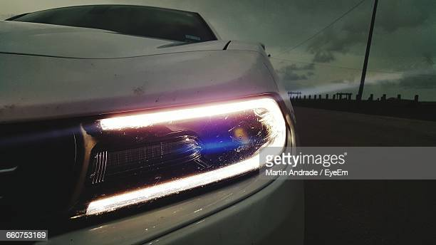 Illuminated Led Headlight On Car Against Sky At Dusk