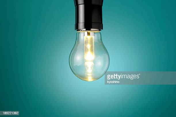 Illuminated LED light bulb against blue background with copy space