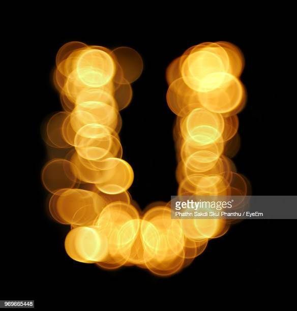 illuminated letter u against black background - letter u stock photos and pictures