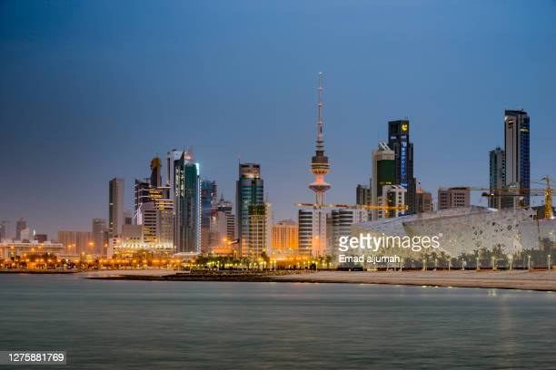 illuminated liberation tower and famous landmark city buildings of kuwait by the sea, kuwait city, capital of kuwait - kuwait city stock pictures, royalty-free photos & images