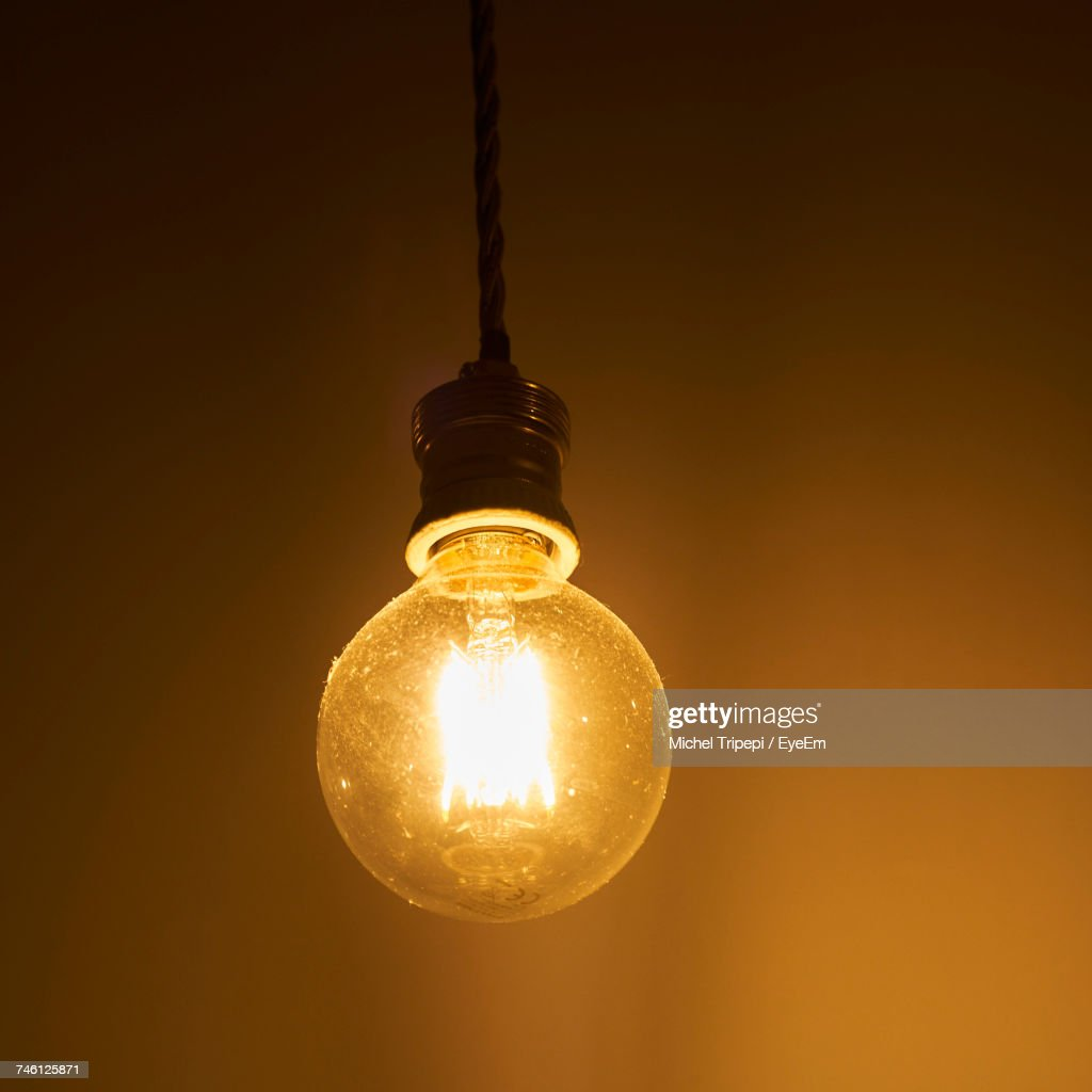 Illuminated light bulb hanging against wall in darkroom stock photo illuminated light bulb hanging against wall in darkroom stock photo aloadofball Image collections