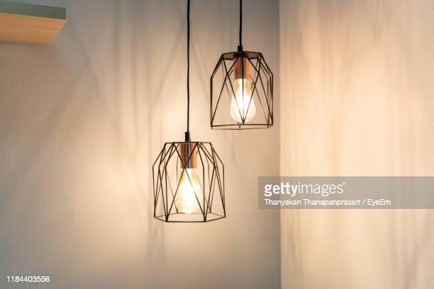 illuminated light bulb hanging on wall at home - pendant light stock pictures, royalty-free photos & images