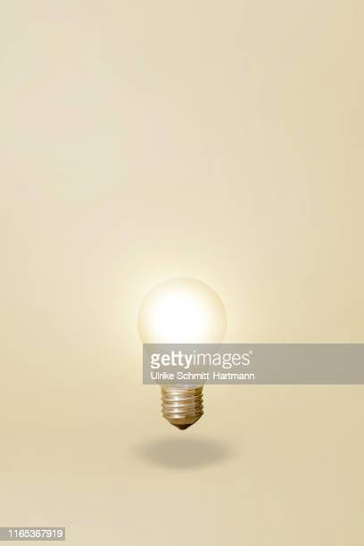 illuminated light bulb - beige background stock pictures, royalty-free photos & images