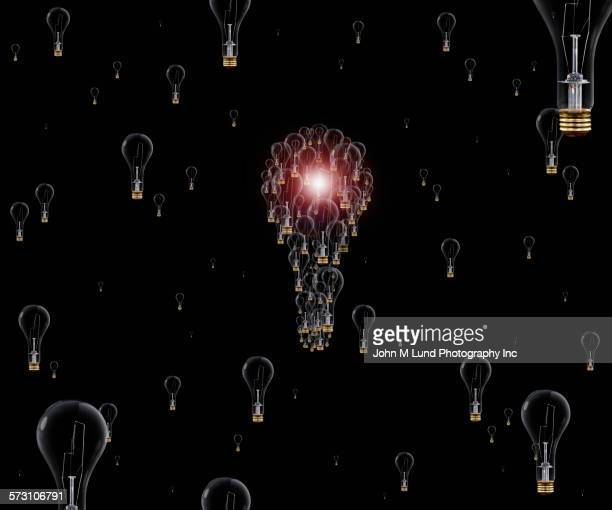 Illuminated light bulbs forming hot air balloon in night sky