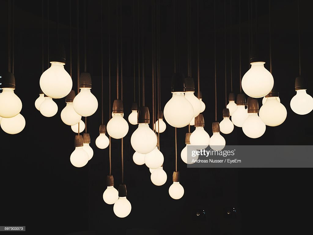 Illuminated Light Bulbs Hanging Against Black Background & Light Bulb Stock Photos and Pictures | Getty Images