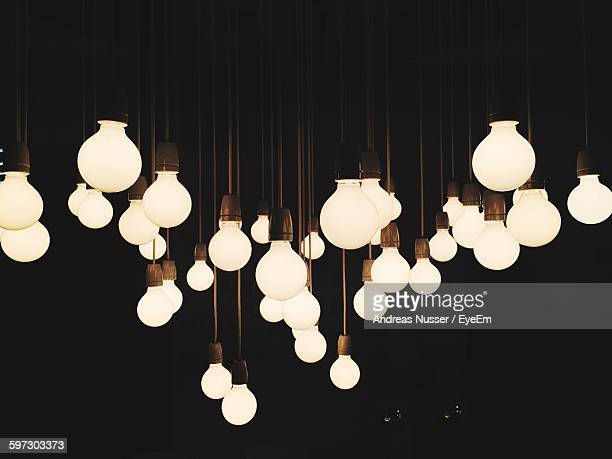 Illuminated Light Bulbs Hanging Against Black Background