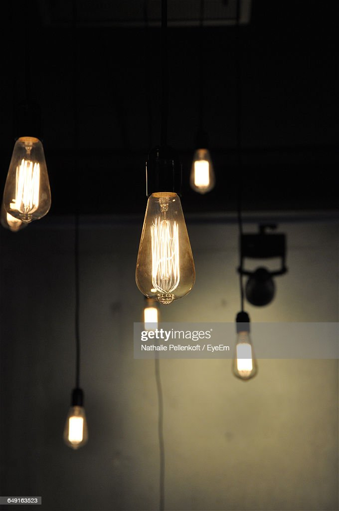 Illuminated Light Bulbs Hanging Against Wall In Room : Stock Photo