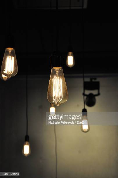 illuminated light bulbs hanging against wall in room - nathalie pellenkoft stock pictures, royalty-free photos & images