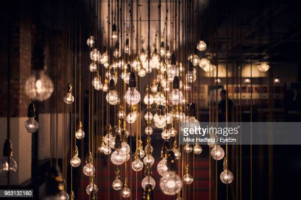illuminated light bulbs hanging in restaurant - filament stock photos and pictures