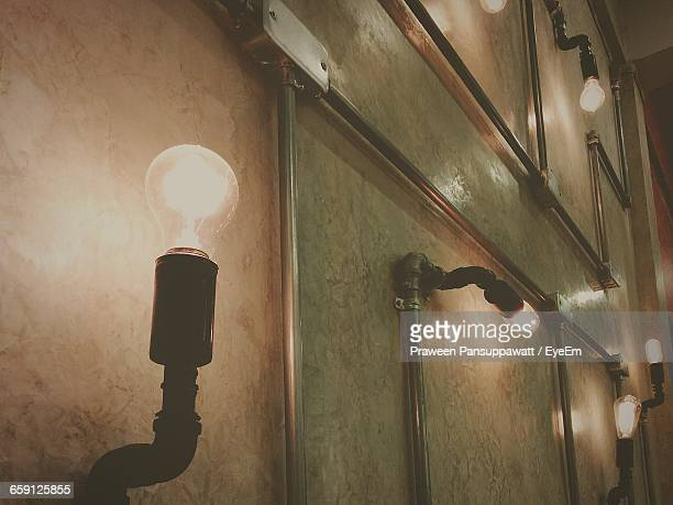 Illuminated Light Bulbs On Wall At Home