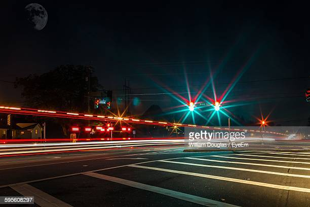 illuminated light trails on city street against sky - william moon stock pictures, royalty-free photos & images