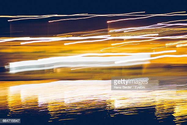 Illuminated Light Trails Reflecting In Pond At Night