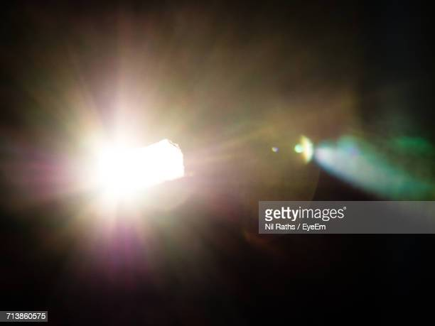 illuminated light with lens flare against black background - blendenfleck stock-fotos und bilder