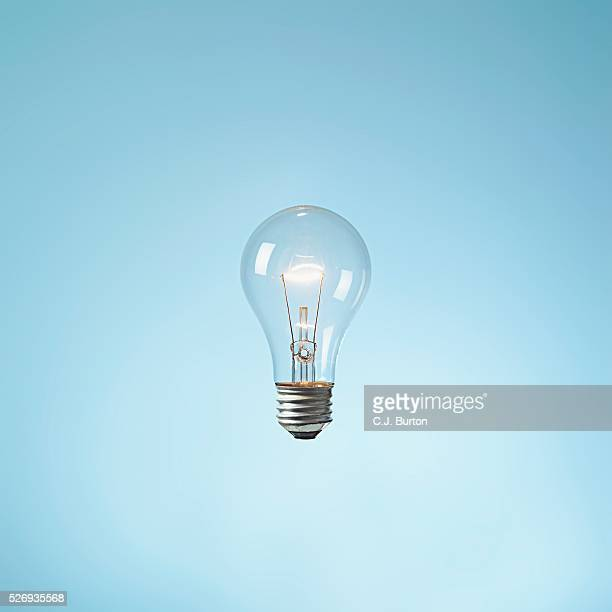 illuminated lightbulb - light bulb stock pictures, royalty-free photos & images