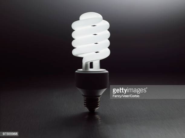 illuminated lightbulb - energy efficient lightbulb stock photos and pictures