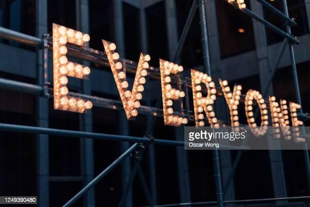 illuminated lightbulb sign in the city at night - text schriftsymbol stock-fotos und bilder