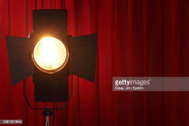 illuminated lighting equipment against red curtain - stage light stock pictures, royalty-free photos & images