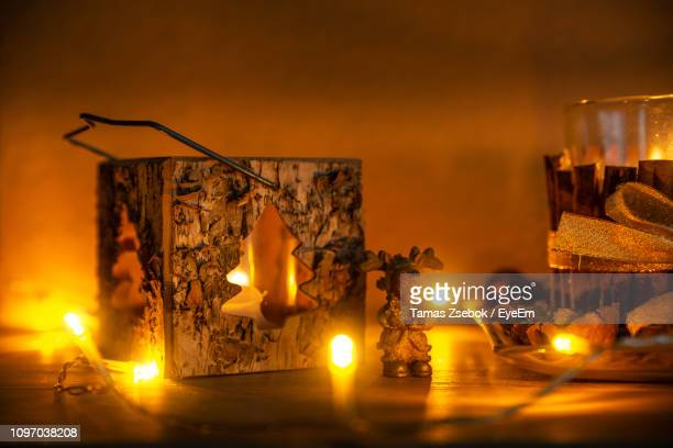 Illuminated Lighting Equipment And Decorations On Table Against Wall At Night