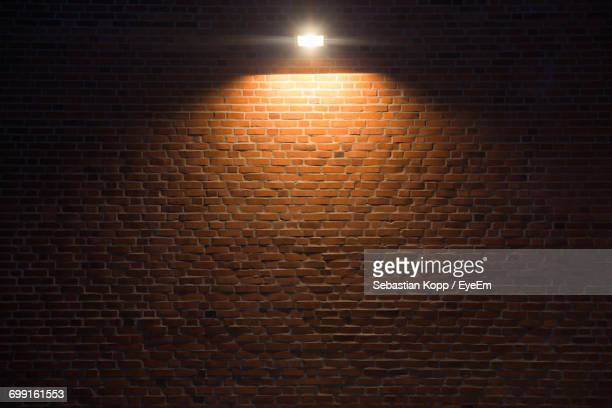 illuminated lighting equipment on brick wall - brick wall stock pictures, royalty-free photos & images