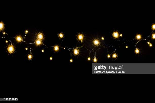 illuminated lights against black background - christmas lights stock pictures, royalty-free photos & images