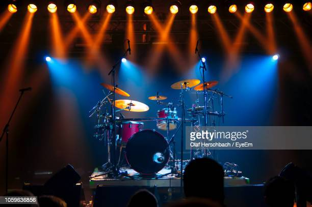 illuminated lights falling on drums at stage during music concert - drum kit stock pictures, royalty-free photos & images