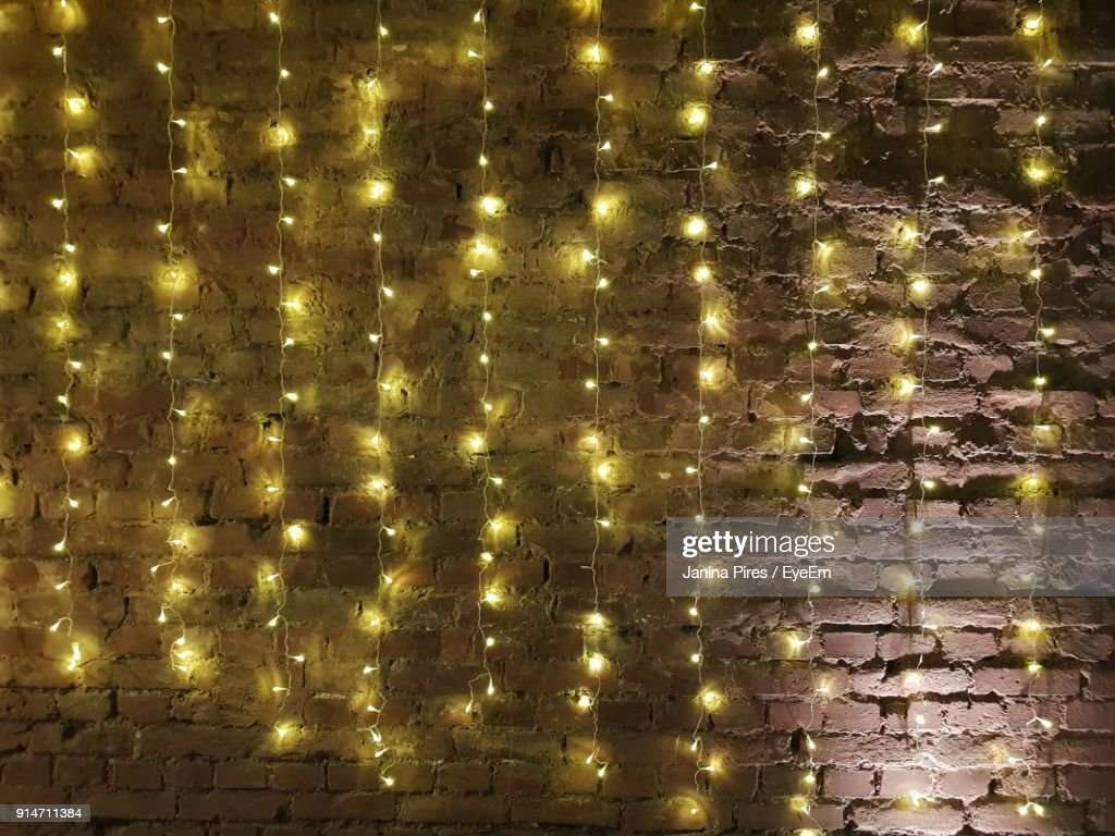 What Can I Use To Attach Christmas Lights To Brick illuminated lights hanging against brick wall high-res stock