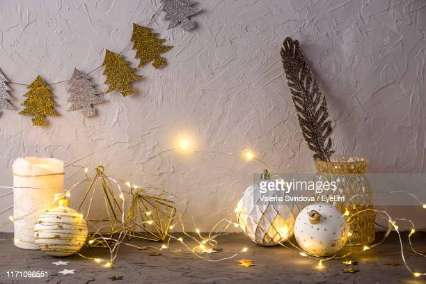illuminated lights on table - christmas decore candle stock pictures, royalty-free photos & images