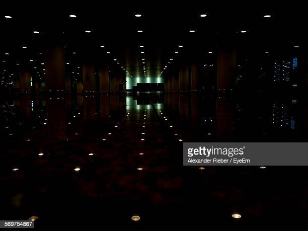 Illuminated Lights Reflecting On Floor Of Corridor