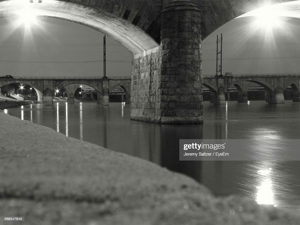 Illuminated Lights Reflection In River Below Bridge At Night : Stock Photo