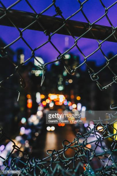 illuminated lights seen through damaged chainlink fence at night - lower east side manhattan stock pictures, royalty-free photos & images