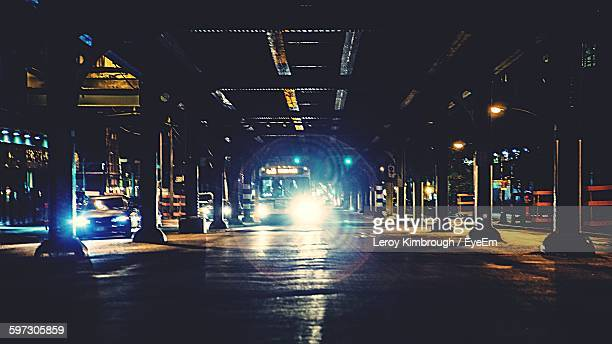 Illuminated Lights Under Bridge In City At Night