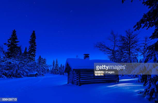 Illuminated log house at night