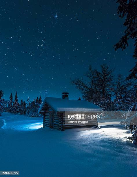 illuminated log house at night - winter house stock pictures, royalty-free photos & images