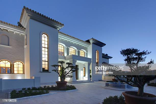 illuminated luxury villa at dusk - villa stock pictures, royalty-free photos & images