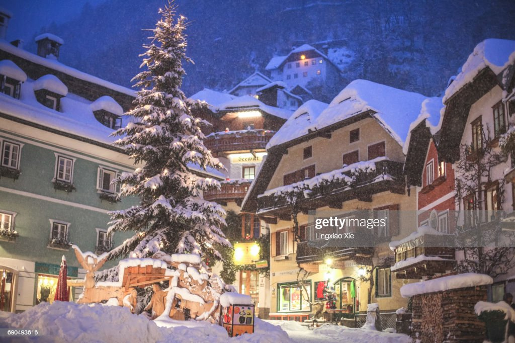 Illuminated Market Square of Hallstatt snowing at night, Austria : Stock Photo