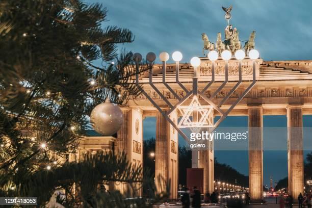 simbolo menorah illuminato e albero di natale davanti alla porta di brandeburgo a berlino contro il cielo delle ore blu - porta cittadina foto e immagini stock